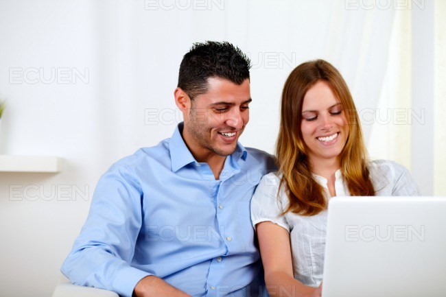 Lovely couple smiling and using a laptop stock photo