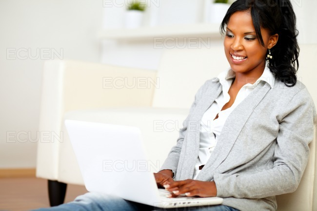 Lovely student girl smiling and looking to laptop stock photo