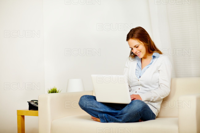 Lovely woman on sofa with a laptop stock photo