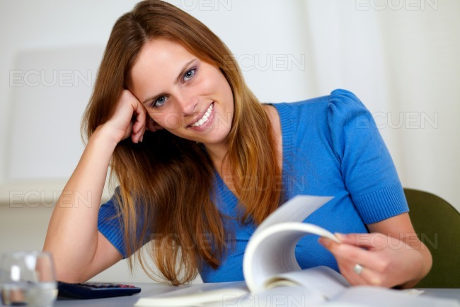 Lovely young female reading at home stock photo