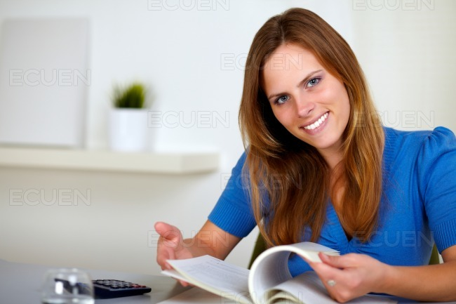 Lovely young woman reading a book at home stock photo