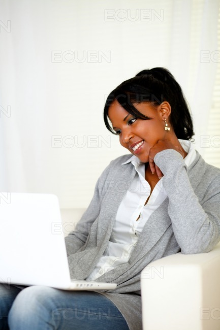 Lovely young woman smiling and looking to laptop stock photo