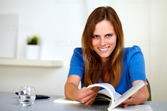 Lovely young woman smiling and reading a book stock photo