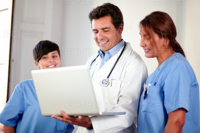 Medical team using a laptop while standing