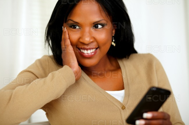 Pensive black woman using her cellphone stock photo