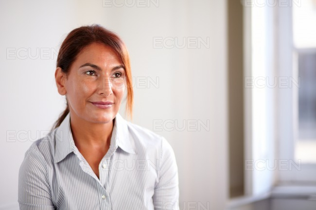 Pensive mature woman smiling and thinking