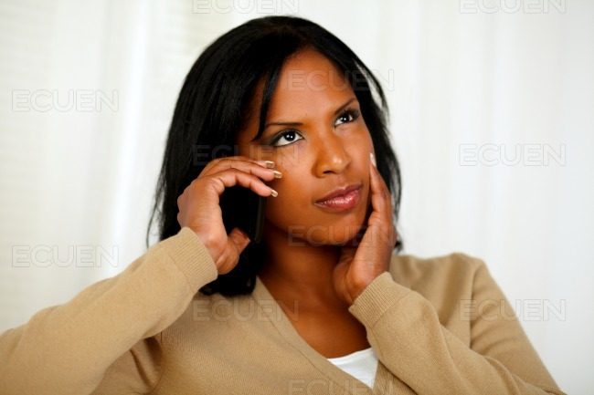 Pensive young woman conversing on cellphone stock photo