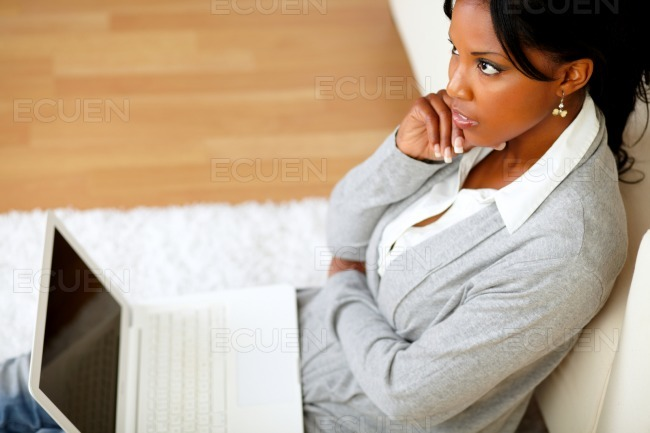 Pensive young woman is sitting on the floor stock photo