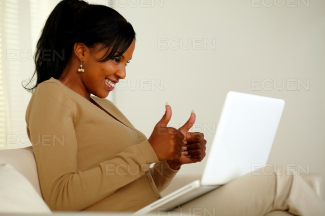 Positive young woman looking to laptop screen stock photo