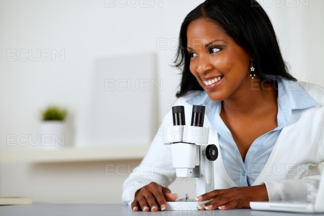 Pretty black woman working with a microscope stock photo