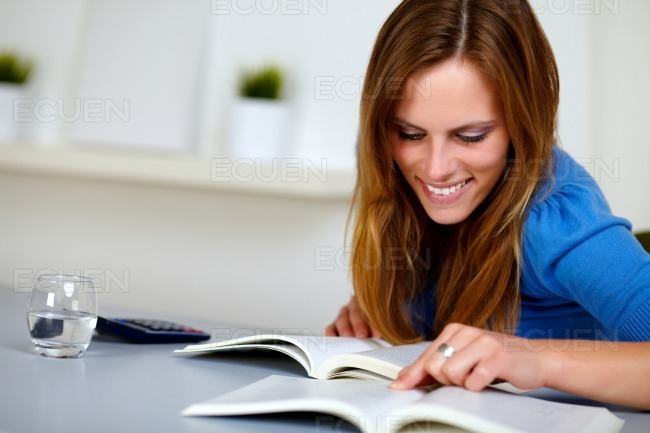 Pretty blonde student woman smiling and reading stock photo