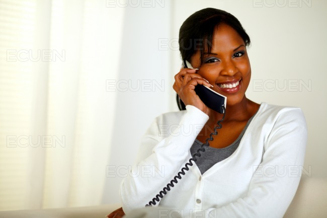 Pretty girl smiling at you while speaking on phone stock photo
