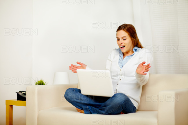 Pretty girl working on sofa with a laptop stock photo