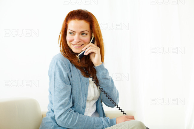 Pretty lady smiling and using a phone stock photo