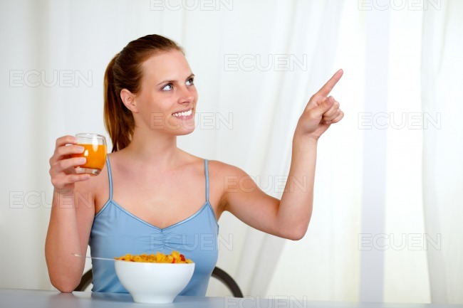 Pretty lovely woman eating meal and pointing