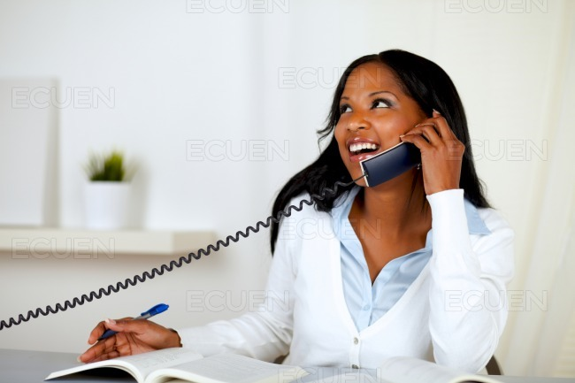 Pretty lovely young woman smiling on phone stock photo