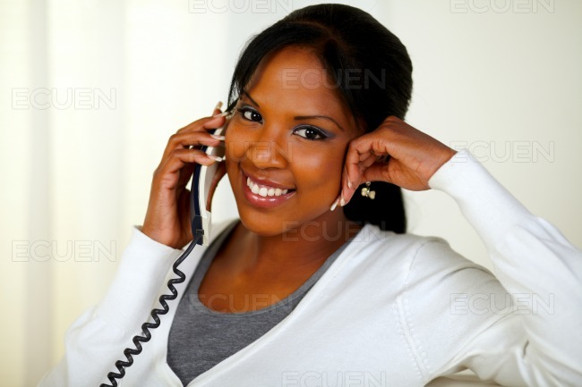 Pretty woman looking at you while talking on phone stock photo