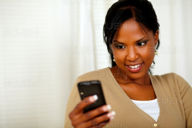 Pretty woman reading a text message by the mobile stock photo