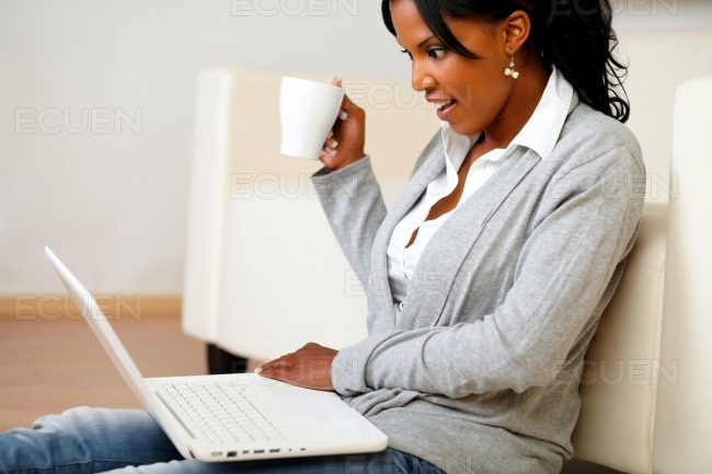 Pretty woman with a mug browsing the Internet stock photo