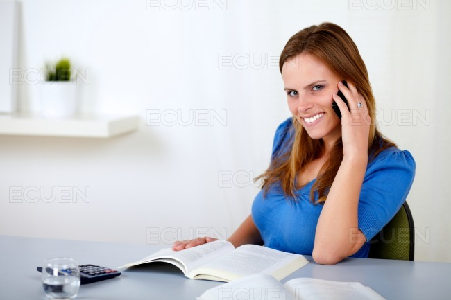 Pretty young girl speaking and browsing a book stock photo