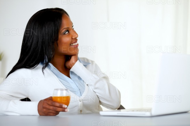 Pretty young woman looking up with an orange juice stock photo