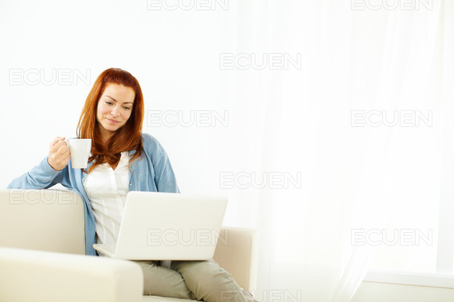 Pretty young woman resting alone on laptop stock photo