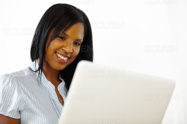Pretty young woman using a laptop stock photo