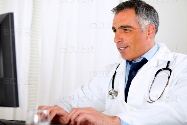 Professional latin doctor using a computer stock photo