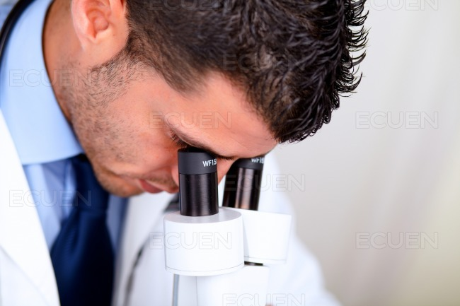 Professional medical man using a microscope stock photo