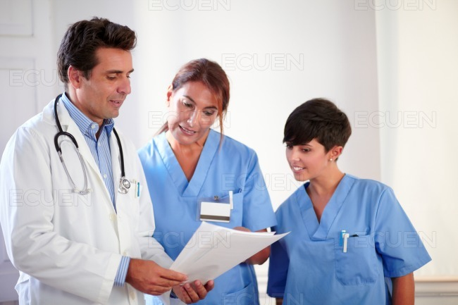 Professional medical team looking at documents stock photo