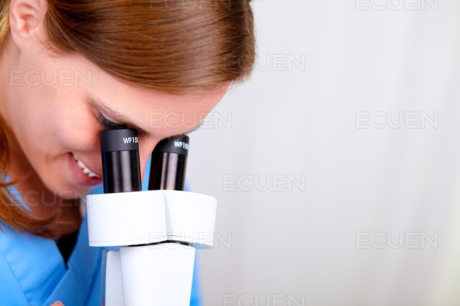 Professional medical woman using a microscope stock photo
