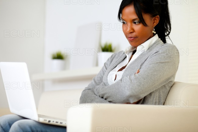Reflective young woman reading on screen stock photo