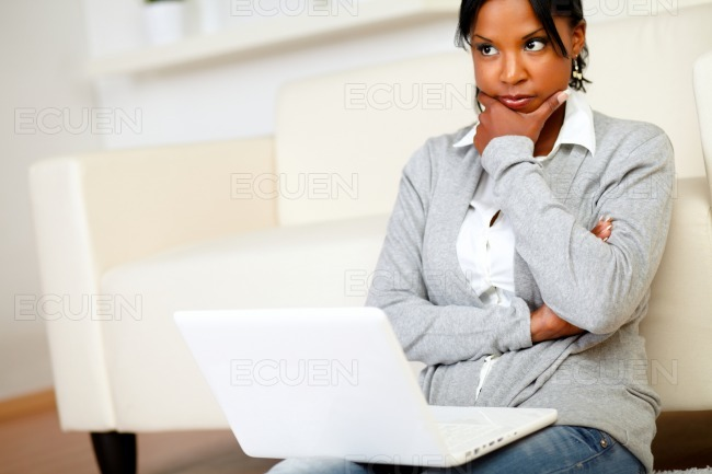 Reflective young woman sits on the floor stock photo
