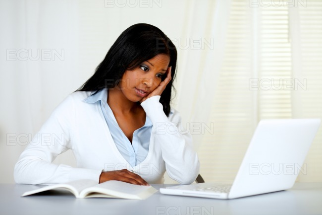 Reflective young woman studying on laptop stock photo