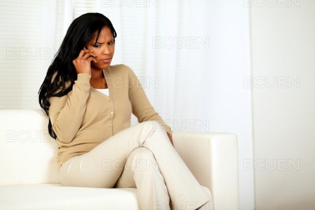 Reflexive young woman conversing on cellphone stock photo