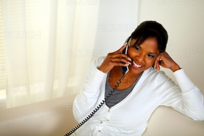 Relaxed black girl smiling and conversing on phone stock photo