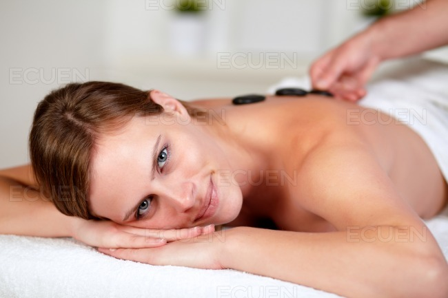 Relaxed female receiving a massage at spa stock photo