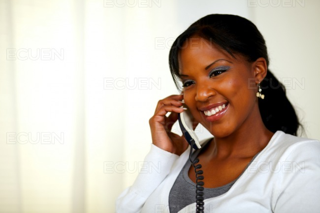 Relaxed female smiling and conversing on phone stock photo