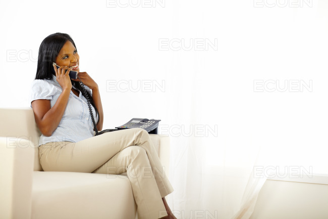 Relaxed pretty young lady speaking on phone stock photo