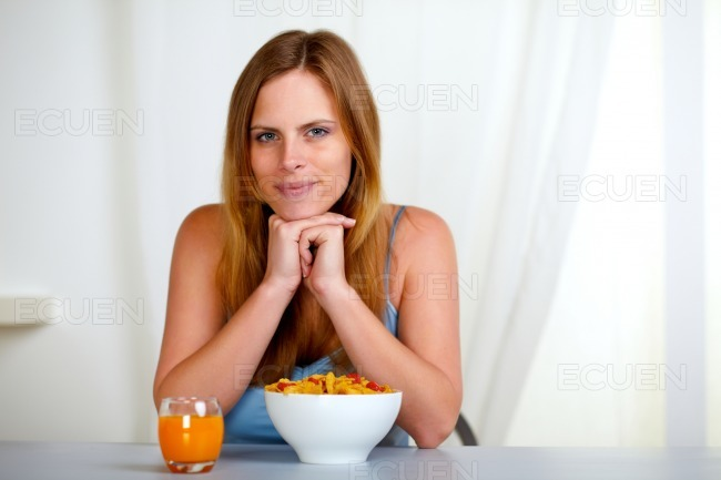 Relaxed pretty young woman at breakfast stock photo