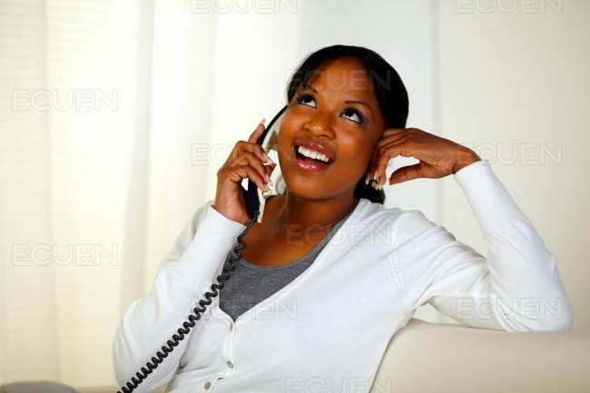 Relaxed pretty young woman conversing on phone stock photo
