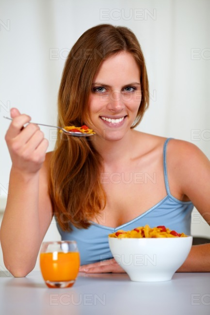 Relaxed pretty young woman eating breakfast stock photo