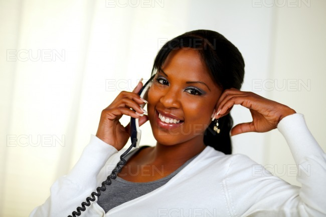 Relaxed woman looking at you and speaking on phone stock photo
