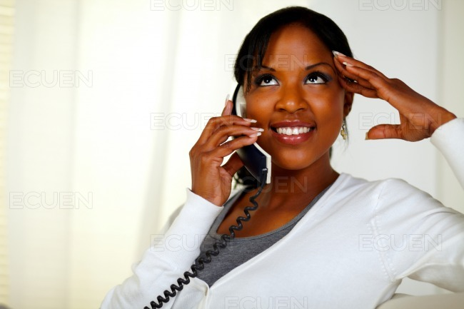 Relaxed woman looking up and conversing on phone stock photo