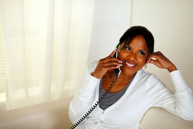 Relaxed woman smiling and conversing on phone stock photo