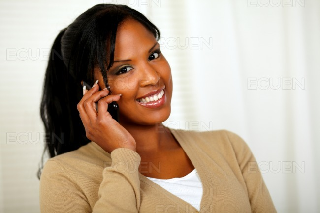 Relaxed woman smiling at you with a cellphone stock photo