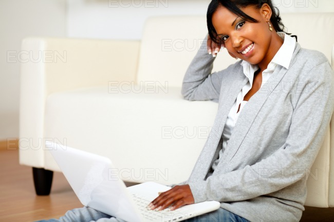 Relaxed woman smiling at you with a laptop stock photo