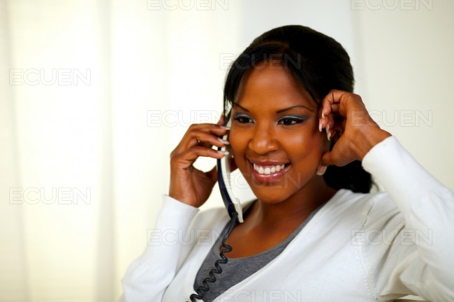 Relaxed young black woman speaking on phone stock photo