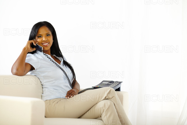 Relaxed young lady speaking on phone stock photo
