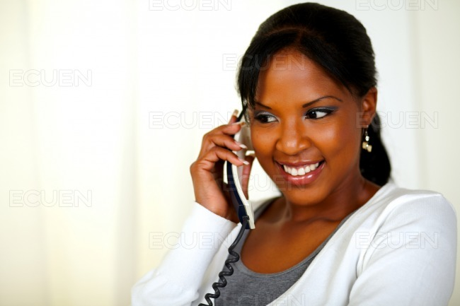 Relaxed young woman conversing on phone stock photo